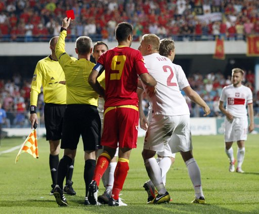 Referee Kristinn Jakobsson of Iceland (2nd L) shows a red card to Poland's Ludovic Obraniak (C) during their World Cup 2014 qualifying soccer match against Montenegro in Podgorica