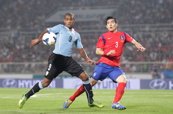 GOYANG, SOUTH KOREA - SEPTEMBER 08: Diego Rolan of Uruguay competes for the ball with Kim Ju-Young of South Korea during the international friendly match between South Korea and Uruguay at Goyang Stadium on September 8, 2014 in Goyang, South Korea. (Photo by Chung Sung-Jun/Getty Images)